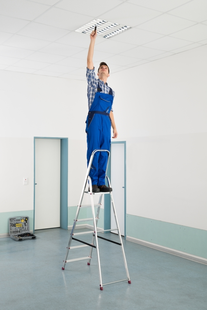 Male Electrician On Ladder Installing Ceiling Light 687x1030